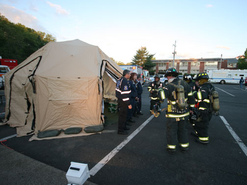Firefighters congregate outside of a DRASH rehab shelter during the May 19 Eight Department fire drill.